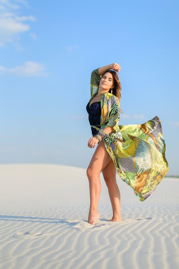 Jonge vrouw die groene strandrobe dragen die zich op wit zand in D bevinden stock fotografie