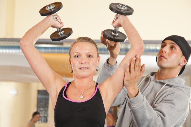 Jonge vrouw die in gymnastiek met trainer uitoefent royalty-vrije stock afbeelding