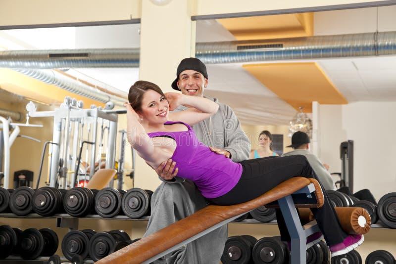 Jonge vrouw die in gymnastiek met trainer uitoefent royalty-vrije stock afbeeldingen