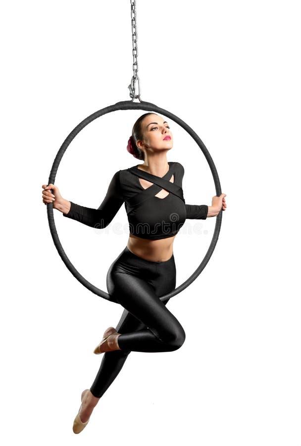 Jonge vrouw die gymnastiek- oefeningen op de hoepel doen stock afbeelding
