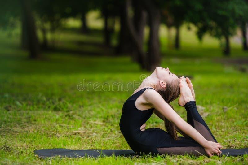 Jonge vrouw die gymnastiekyoga doen en zich in het stadspark uitrekken op zonsondergang stock foto's
