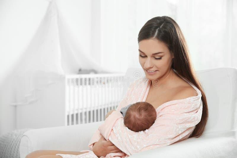Jonge vrouw die haar baby in kinderdagverblijf de borst geven royalty-vrije stock fotografie