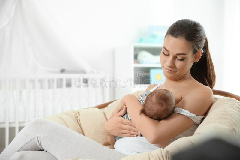Jonge vrouw die haar baby in kinderdagverblijf de borst geven stock fotografie
