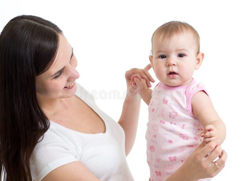 Jonge vrouw die haar babydochter bekijken Het spelen van de moeder met jong geitje stock foto