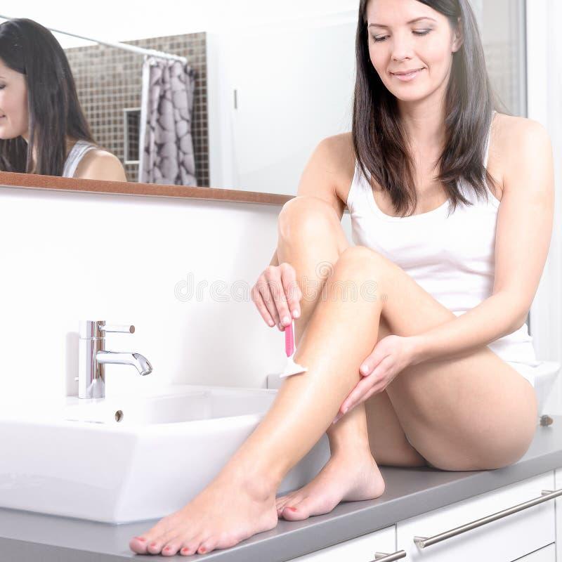 Jonge vrouw die haar benen scheren bij wasbak stock foto