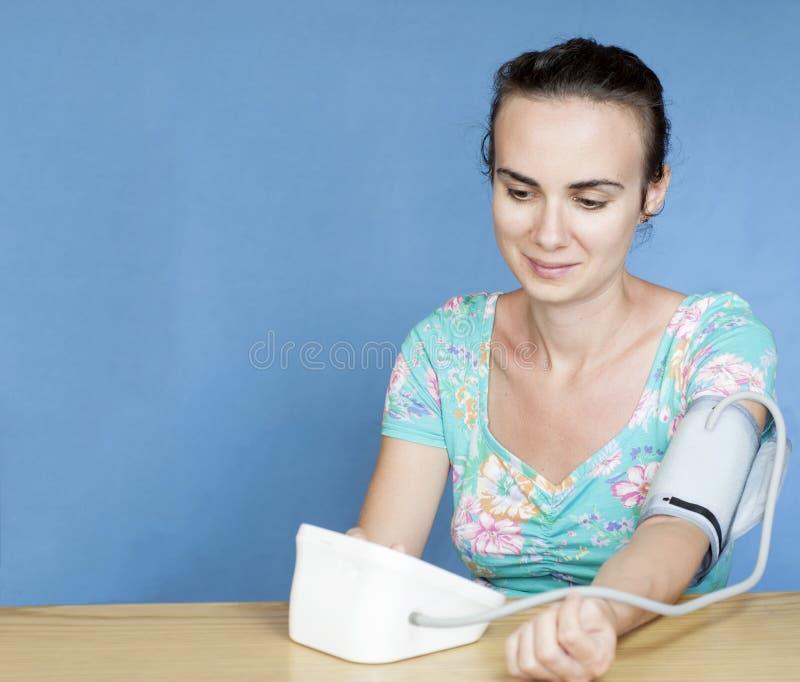 Jonge vrouw die haar bloeddruk meten royalty-vrije stock foto