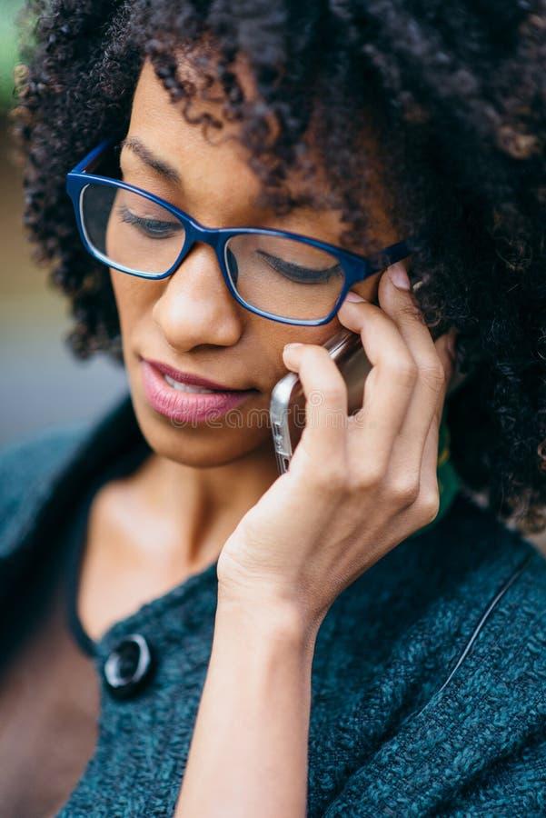 Jonge vrouw die haar celtelefoon met behulp van stock fotografie