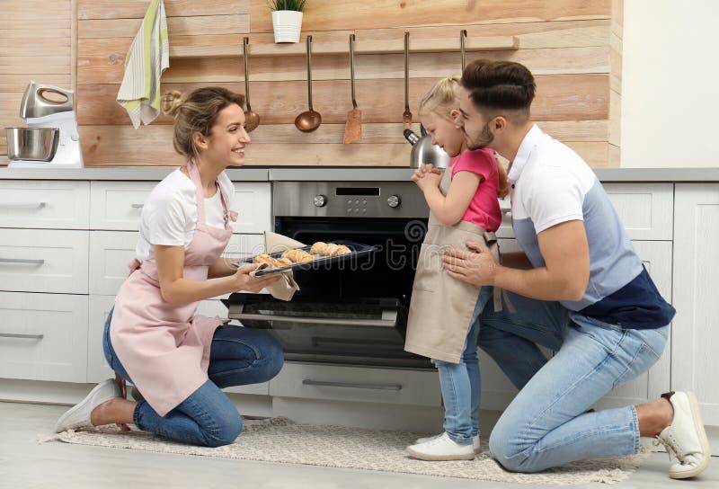 Jonge vrouw die haar familie behandelen met eigengemaakte oven gebakken koekjes stock afbeeldingen