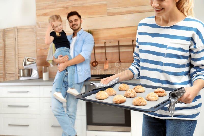 Jonge vrouw die haar familie behandelen met eigengemaakte oven gebakken koekjes stock afbeelding