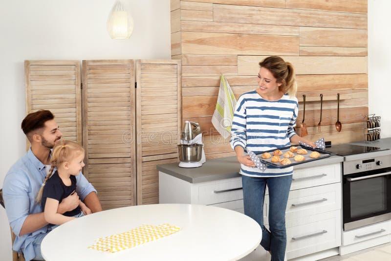 Jonge vrouw die haar familie behandelen met eigengemaakte oven gebakken koekjes royalty-vrije stock afbeeldingen