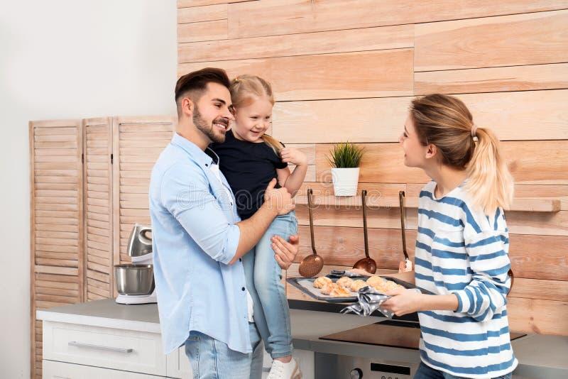 Jonge vrouw die haar familie behandelen met eigengemaakte oven gebakken koekjes stock fotografie
