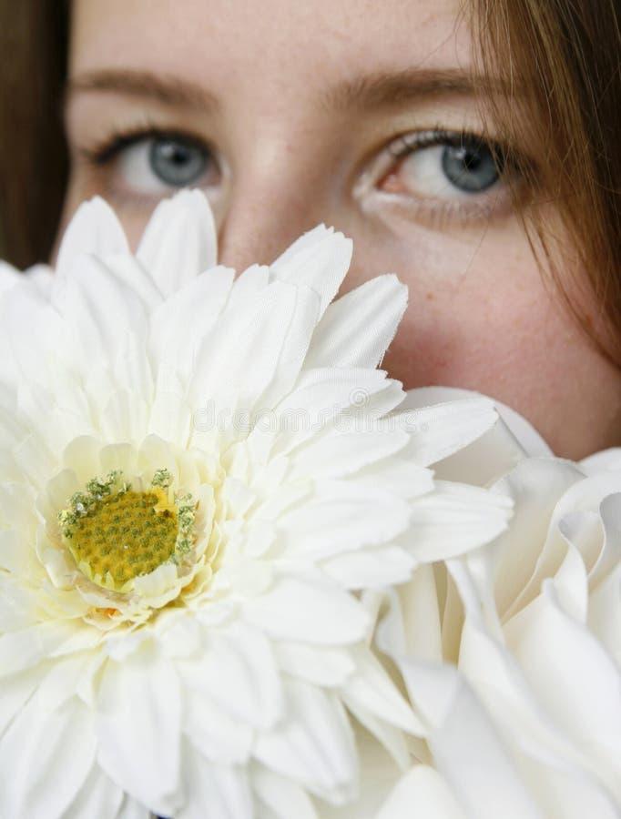 Jonge vrouw die haar gezicht met witte bloemen verbergt royalty-vrije stock fotografie