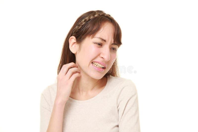 Jonge vrouw die haar hals krassen royalty-vrije stock foto's