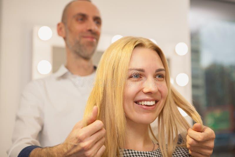 Jonge vrouw die haar die haar hebben door kapper wordt gestileerd stock foto
