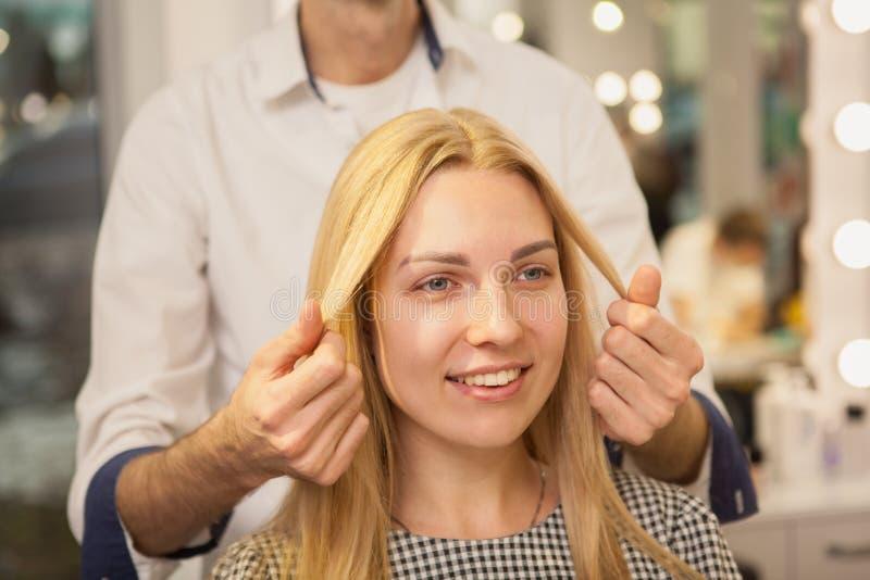 Jonge vrouw die haar die haar hebben door kapper wordt gestileerd stock foto's