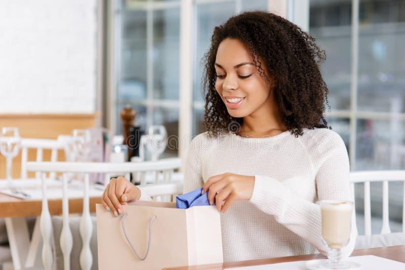 Jonge vrouw die haar het winkelen zak controleren stock afbeelding