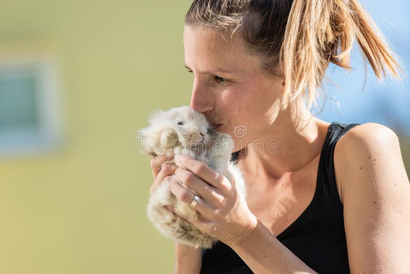 Jonge vrouw die haar huisdierenkonijntje kussen royalty-vrije stock fotografie