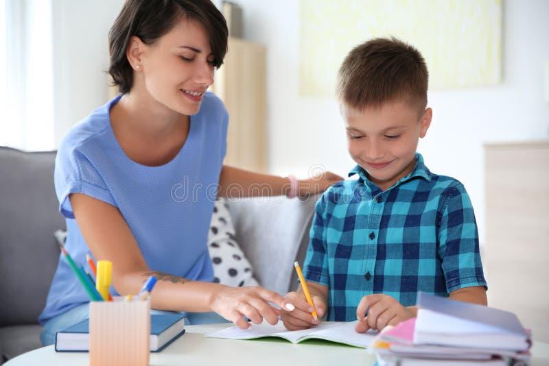 Jonge vrouw die haar kind met thuiswerk helpen stock afbeelding