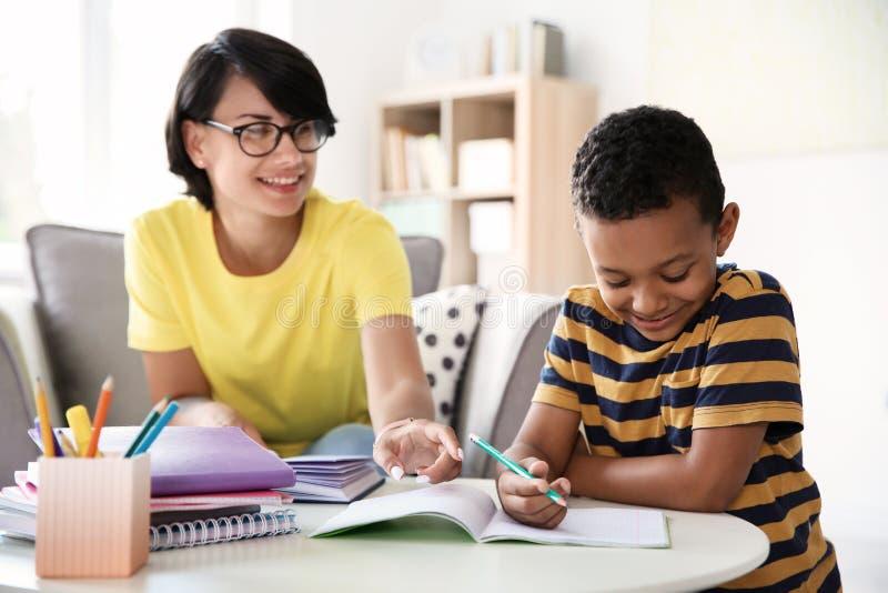 Jonge vrouw die haar kind met thuiswerk helpen royalty-vrije stock afbeelding