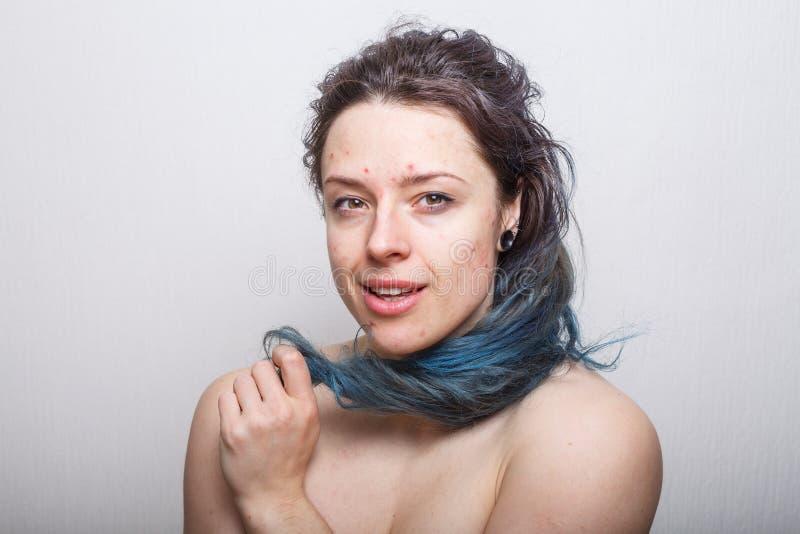 Jonge vrouw die haar kleurrijk maar beschadigd slordig haar op haar vinger rollen stock foto's