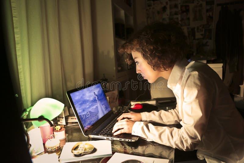 Jonge vrouw die haar laptop bekijken stock foto