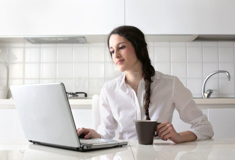 Jonge vrouw die haar laptop bekijkt stock foto