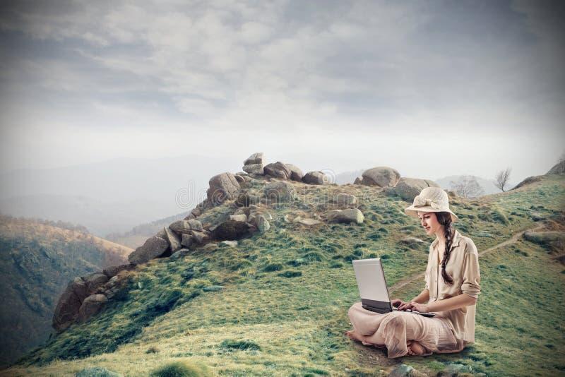 Jonge vrouw die haar laptop met behulp van royalty-vrije stock afbeeldingen