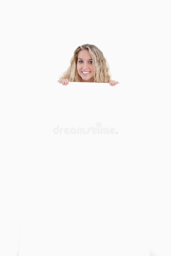 Jonge vrouw die haar lichaam achter een lege affiche verbergt