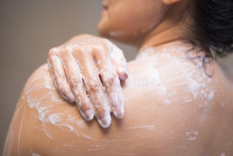 Jonge vrouw die haar lichaam met douchegel wassen stock foto's