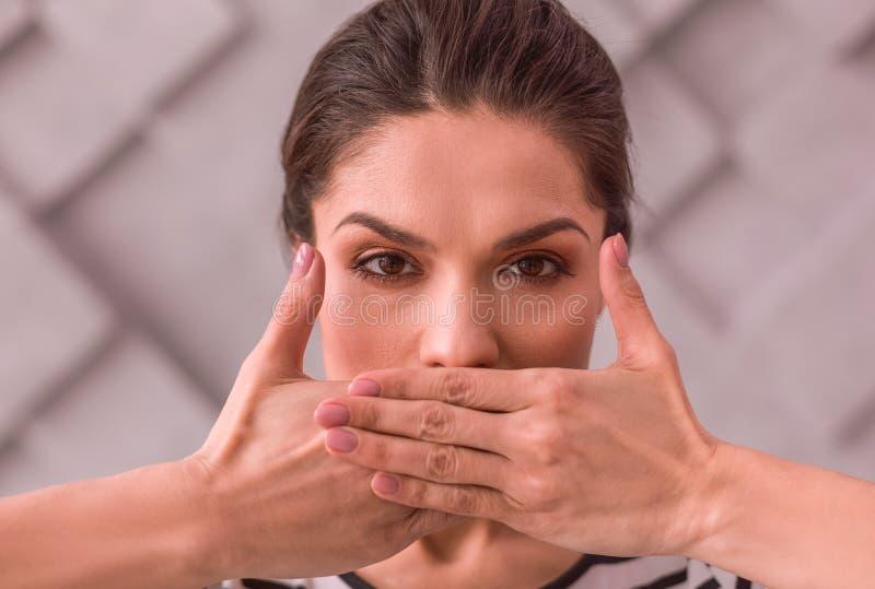 Jonge vrouw die haar mond behandelt met handen stock foto