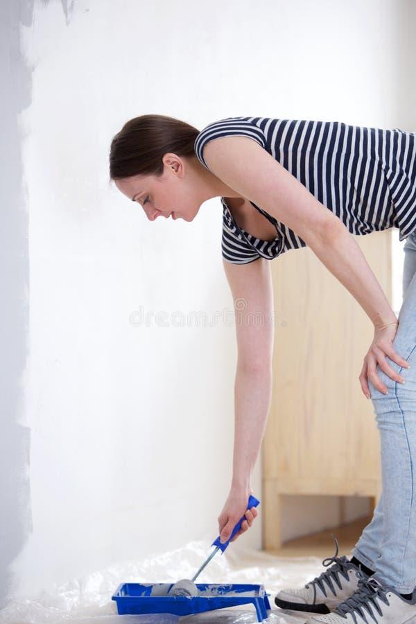 Jonge vrouw die haar nieuw huis opknappen stock foto
