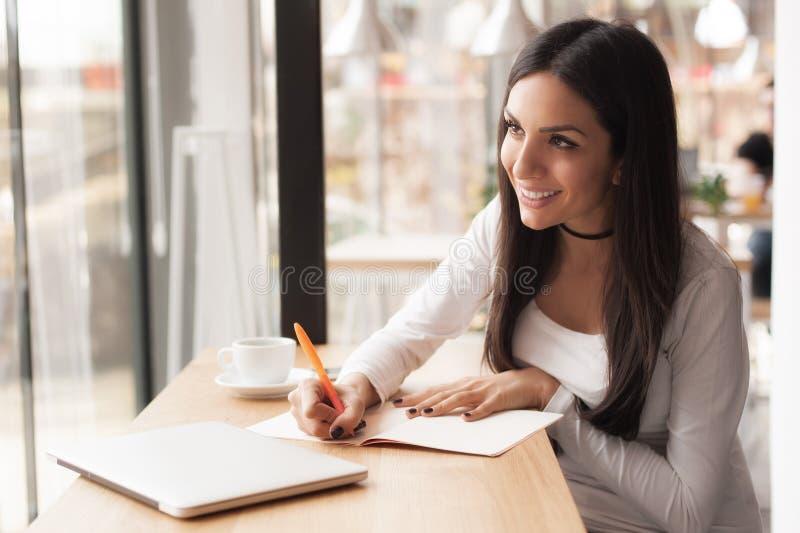 Jonge vrouw die in haar notitieboekje en het drinken ochtendkoffie schrijven stock foto's