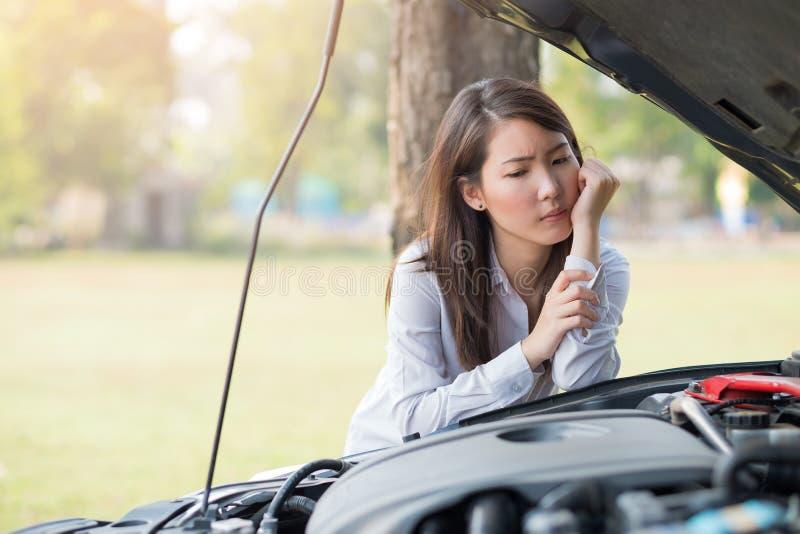 Jonge vrouw die haar opgesplitste auto bekijken royalty-vrije stock afbeeldingen