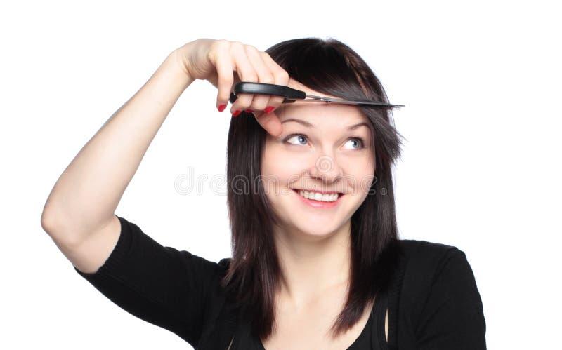 Jonge vrouw die haar rand snijdt royalty-vrije stock afbeeldingen