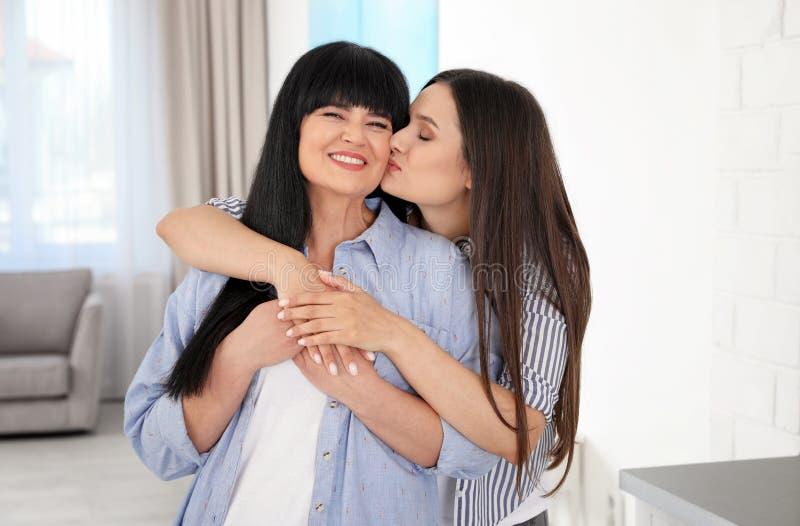 Jonge vrouw die haar rijpe moeder kussen royalty-vrije stock foto