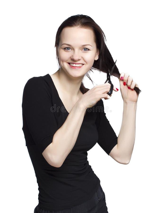 Jonge vrouw die haar snijdt stock foto