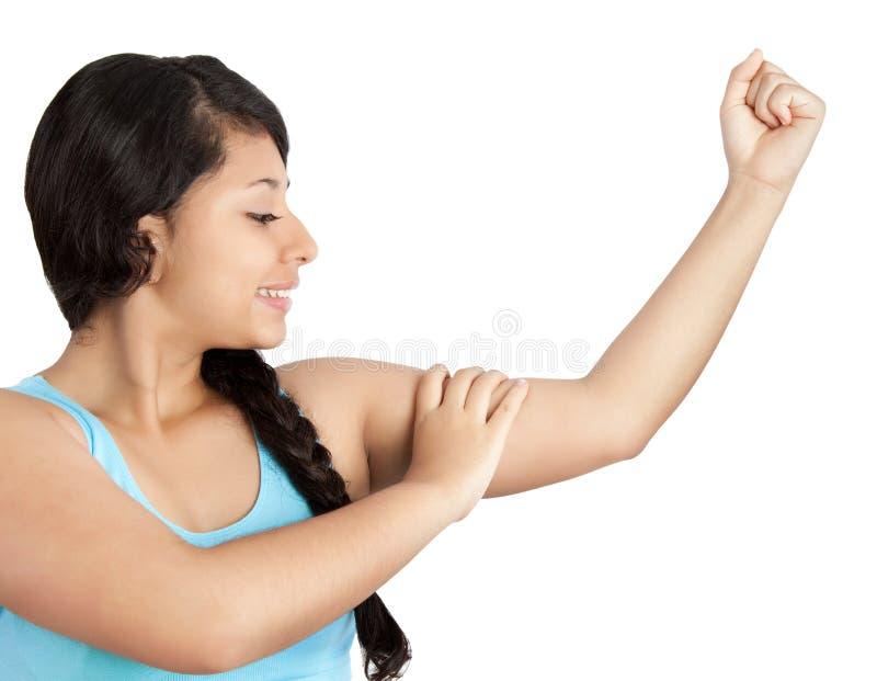 Jonge vrouw die haar spieren toont stock foto