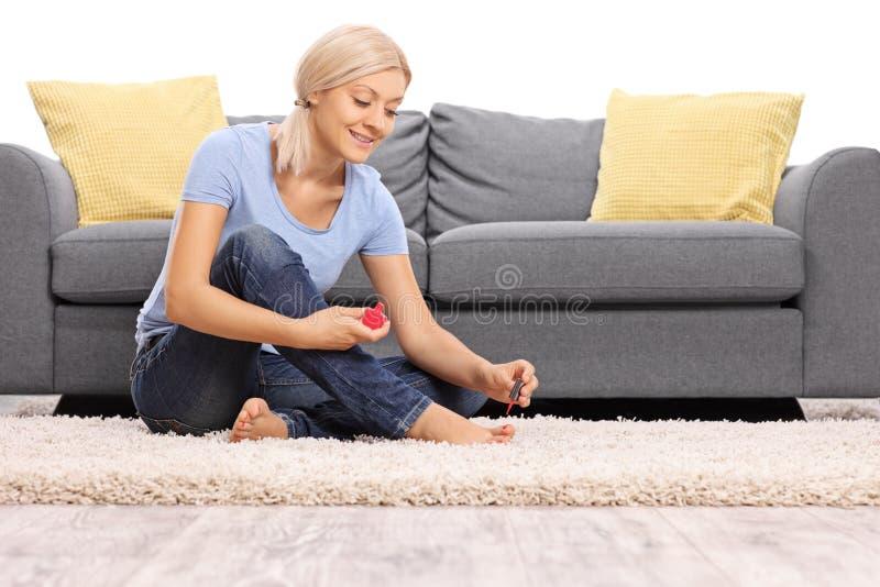 Jonge vrouw die haar teennagels oppoetsen stock afbeeldingen