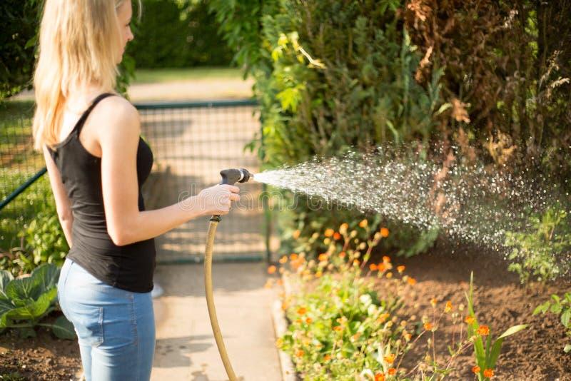 Jonge vrouw die haar tuin gieten stock foto's