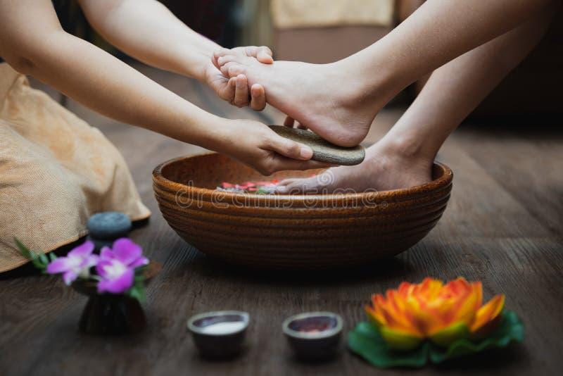 Jonge vrouw die haar die voeten hebben in schoonheidssalon worden geschrobd, Vrouwelijke voeten bij de procedure van de kuuroordp stock afbeelding