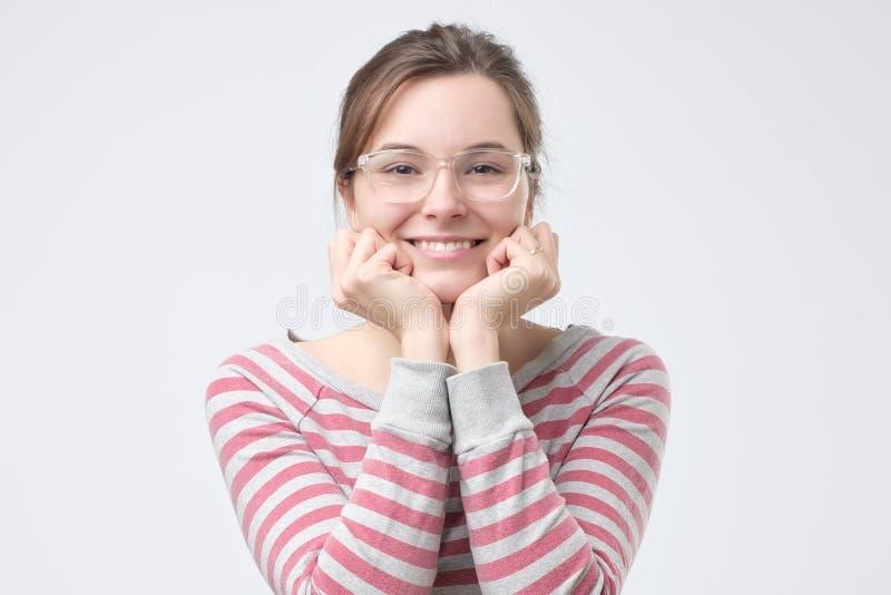 Jonge vrouw die haar vuisten houden aan haar kin in een uitdrukking van opwinding royalty-vrije stock foto's