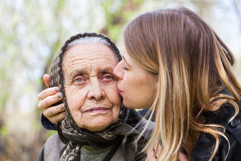 Jonge vrouw die haar zieke grootmoeder kussen stock foto's