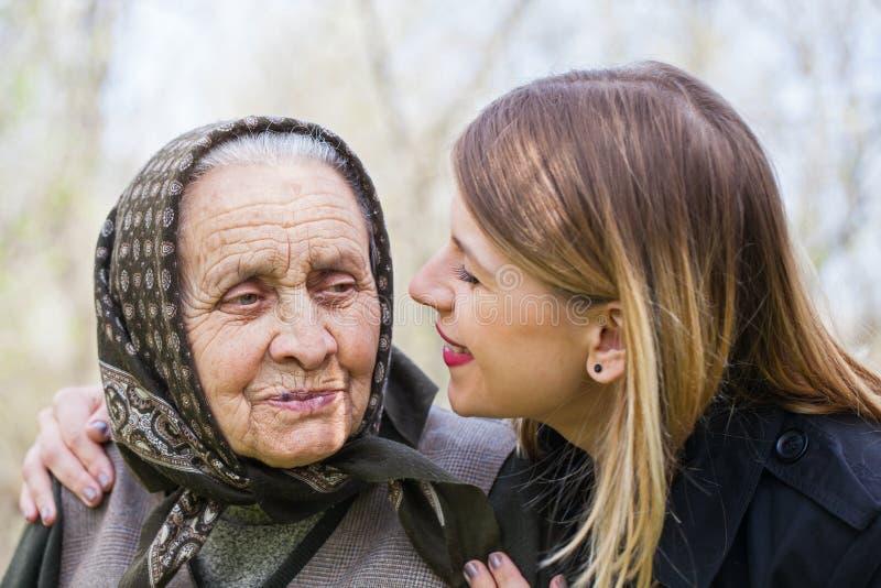 Jonge vrouw die haar zieke grootmoeder kussen royalty-vrije stock foto