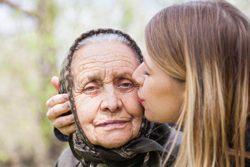 Jonge vrouw die haar zieke grootmoeder kussen stock foto