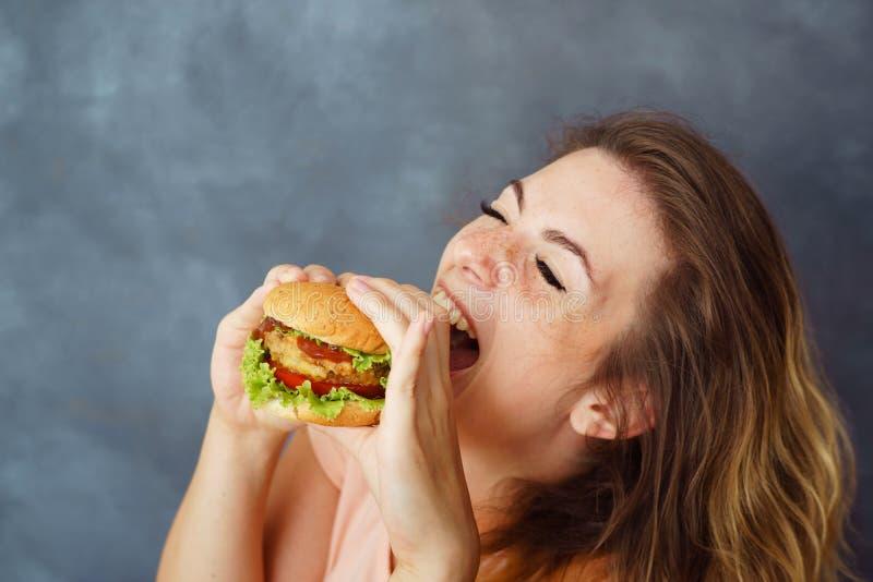 Jonge vrouw die hamburger eten die van de smaak genieten stock fotografie