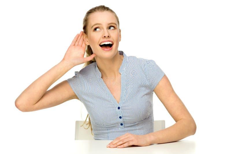 Jonge vrouw die hand zet aan oor stock fotografie