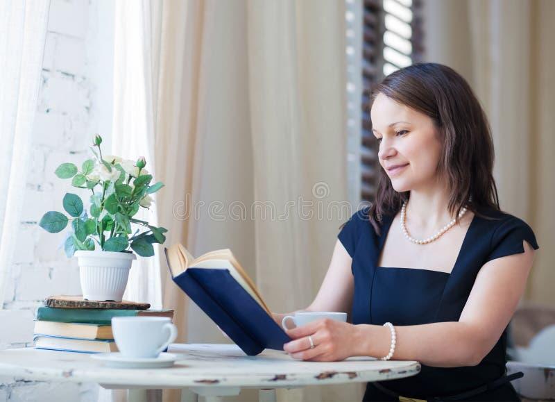 Jonge vrouw die het boek lezen en koffie drinken royalty-vrije stock afbeelding