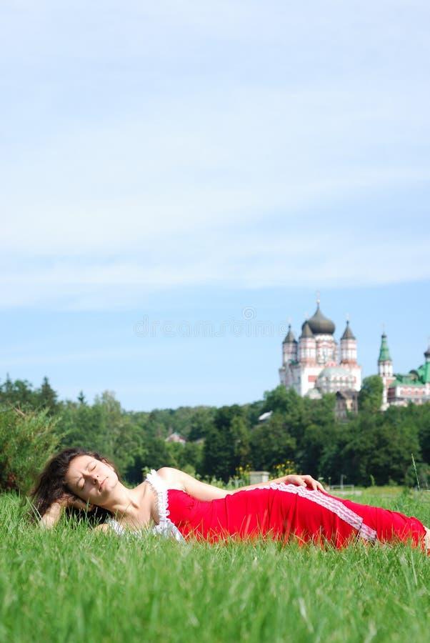 Jonge vrouw die in het gras ligt. royalty-vrije stock afbeeldingen