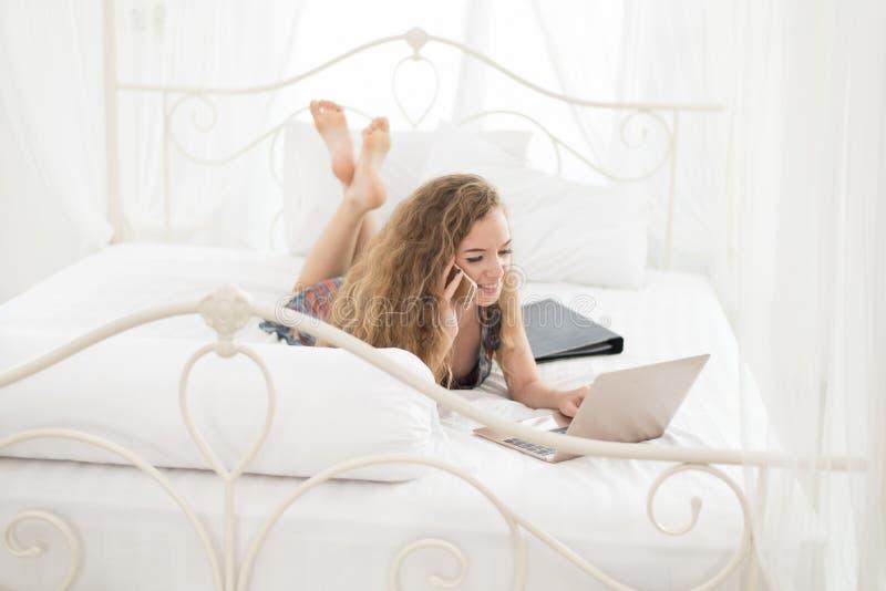 Jonge vrouw die in het huis werken, uitnodigend mobiele telefoon en ons royalty-vrije stock afbeeldingen