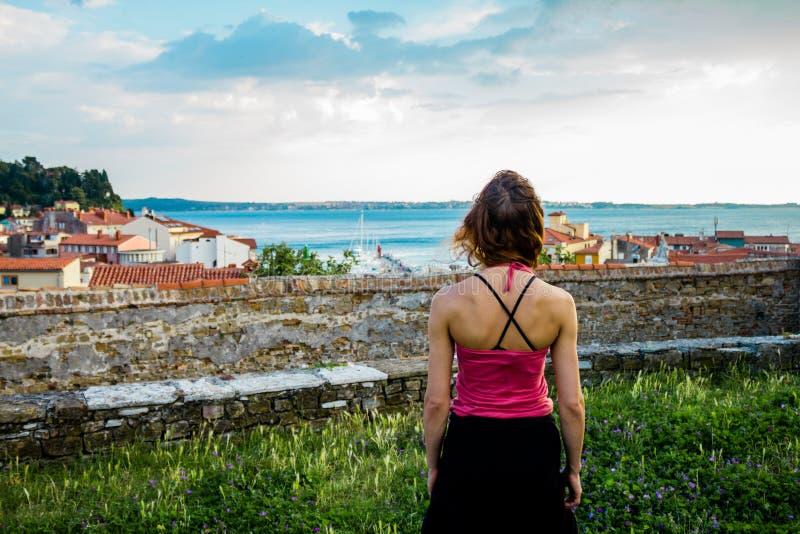 Jonge vrouw die het overzees en haar klein dorp van een heuvel bekijken royalty-vrije stock foto